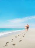 Liebevolle Paare, die mit Abdrücken in Meer gehen Lizenzfreie Stockfotografie