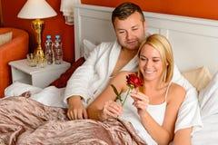 Liebevolle Paare, die rosafarbenes Bett des romantischen Jahrestages feiern Stockfoto