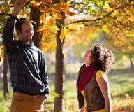 Liebevolle Paare, die Spaß im herbstlichen Park haben stockfoto