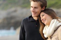 Liebevolle Paare, die weg auf dem Strand schauen Stockfotografie