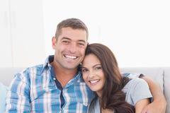 Liebevolle Paare, die zu Hause lächeln Stockbild