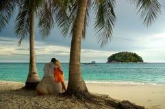 Liebevolle Paare, die zur Insel im Meer schauen Stockfotos