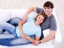 Liebevolle Paare, die zusammen auf dem Sofa liegen Stockfoto