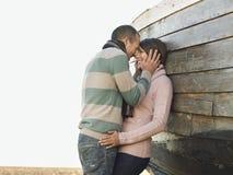Liebevolle Paare gegen hölzernen Rumpf des Bootes Stockbilder