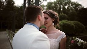 Liebevolle Paare an ihrem Hochzeitstag in der Sommerzeit, einander küssend und zart betrachten Glückliche Braut und Bräutigam stock video