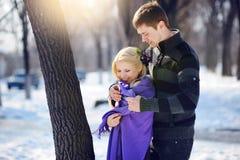 Liebevolle Paare im Wintermann, zum sich von  um einer Frau zu kümmern Stockfotos