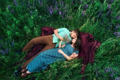 Liebevolle Paare liegen zusammen auf einer Wiese Lizenzfreies Stockfoto