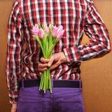 Liebevolle Paare - Mann mit den Blumen, die seine Frau warten. Lizenzfreie Stockfotos