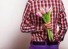 Liebevolle Paare - Mann mit den Blumen, die seine Frau warten. Stockfoto