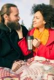 Liebevolle Paare mit den heißen Getränken, die auf Bank im Winter sitzen Lizenzfreie Stockfotos