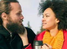 Liebevolle Paare mit den heißen Getränken, die auf Bank im Winter sitzen Stockfotos