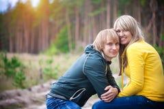 Liebevolle Paare sitzen im sonnigen Park stockfotografie