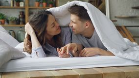 Liebevolle Paarfreundin und Freund und Lügen im Bett unter der umfassenden Unterhaltung, dem Lachen und dem Küssen während des gl stock footage