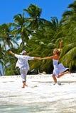 Liebevolle Paarläufe auf einem tropischen Strand Stockfoto