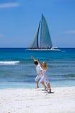 Liebevolle Paarläufe auf einem tropischen Strand Stockbild