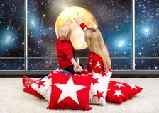 Liebevolle schöne junge Mutter mit dem jungen Sohn, der den Himmel, den Mond, die Sterne betrachtet Sitzen auf schönen weichen Ki Stockfotografie