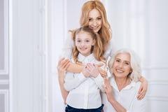 Liebevolle Schönheit, die ihr kleines Mädchen und ältere Mutter umfasst Lizenzfreie Stockfotografie