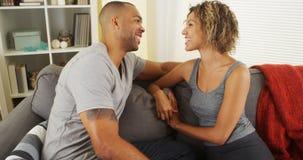 Liebevolle schwarze Paare, die auf Couch sprechen Lizenzfreie Stockfotografie