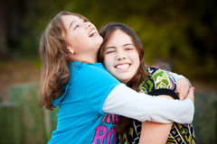 Liebevolle umarmende und lächelnde Schwestern Lizenzfreie Stockfotos