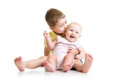 Liebevoller Bruder, der das kleine Schwesterchen an lokalisiert küsst Lizenzfreie Stockbilder