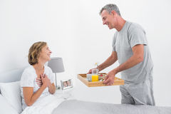 Liebevoller Ehemann, der der Frau Frühstück im Bett holt Stockfotos