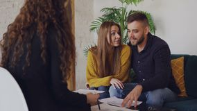 Liebevoller Freund und Freundin betrachten Plan des Hauses, das sie kaufen werden und mit Immobilienmakler sprechen