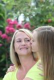 Liebevoller Jugendlicher, der ihre Mutter küsst lizenzfreies stockfoto