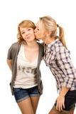 Liebevoller Jugendlicher, der ihrem Freund einen Kuss gibt Lizenzfreie Stockfotografie