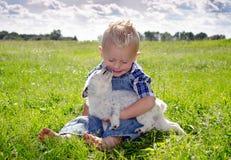 Liebevoller Junge und Welpe des Sommers Stockfoto