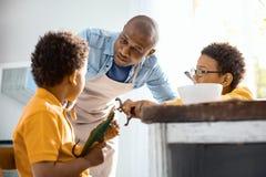 Liebevoller junger Vater, der seine Söhne bittet, sich zu benehmen stockfoto