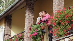 Liebevoller Mann und Frau, die auf dem Balkon mit roten Blumen steht stock video