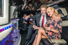 Liebevoller Umhüllungschampagner des jungen Mannes für Freundin in der Limousine Stockfoto