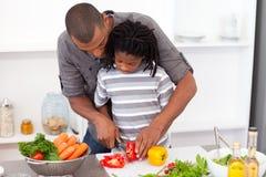 Liebevoller Vater, der seinem Sohnschnittgemüse hilft Stockbild