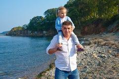 Liebevoller Vater mit der Tochter auf Schultern gehend auf den Strand Stockbilder