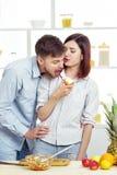 Liebevolles glückliches Paar, das Apfel in der Küche isst Lizenzfreie Stockfotografie