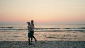 Liebevolles glückliches Paar ist, umfassend laufend, wirbelnd und auf Strand bei Sonnenuntergang stock video footage