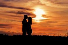 Liebevolles glückliches Paar des schönen Schattens, das bei Sonnenuntergang auf einem Gebiet des warmen Sommertages küsst Lizenzfreie Stockbilder
