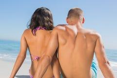 Liebevolles junges Paarsitzen beim Betrachten des Meeres Lizenzfreie Stockfotos