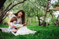 liebevolles Mutterlesebuch zum Kleinkindsohn im Freien auf Picknick im Frühjahr oder Sommerpark Glücklicher Familien- und Muttert stockbild