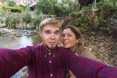 Liebevolles nettes glückliches Paar, das selfie in der Stadt nimmt lizenzfreie stockbilder