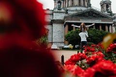 Liebevolles Paar umarmt gegen einen Hintergrund von roten Blumen und von Weinlesearchitektur Lizenzfreie Stockfotos