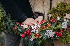 Liebevolles Paarhändchenhalten mit Weihnachtskranz Stockbilder