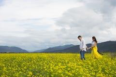 Liebhaber bemannen und Frauenweg auf dem Blumenfeld lizenzfreies stockbild