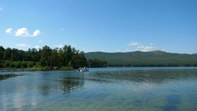 Liebhaber fahren in ein Boot auf einen See Freunde, die sich zusammen auf dem Wasser entspannen Die schöne Natur herum stock video footage