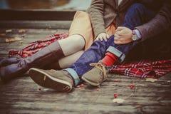 Liebhaber Frau und Mann, die nahe dem See sitzen lizenzfreie stockbilder