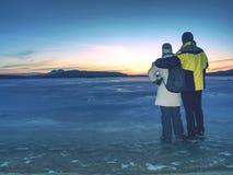 Liebhaber halten sich, auf Eis in gefrorener Lagunen- und Uhrsonne zu bleiben lizenzfreie stockfotos