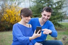 Liebhaber im Park, der den Handy schaut Stockbilder
