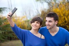 Liebhaber im Park, der Foto mit Handy macht Stockbild