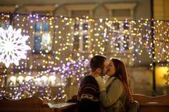 Liebhaber küssen auf dem Hintergrund des Glänzens von festlichen Girlanden Lizenzfreie Stockfotografie