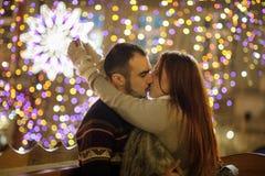 Liebhaber küssen auf dem Hintergrund des Glänzens von festlichen Girlanden Lizenzfreies Stockbild